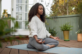 Frau meditiert im Freien, ihre Entspannungstechnik gegen chronische Schmerzen.
