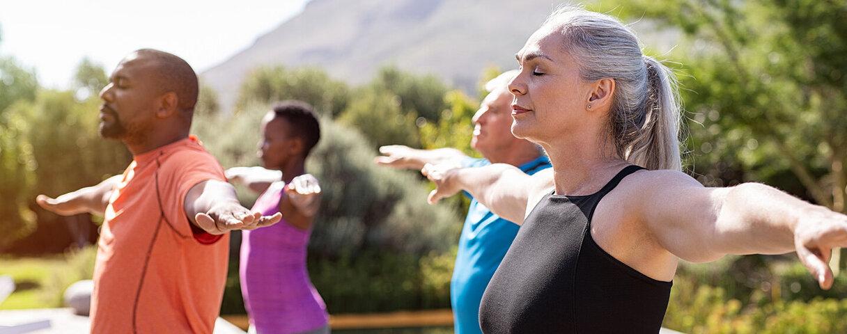 Eine Gruppe älterer Menschen macht gemeinsam Entspannungsübungen.