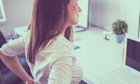 Junge Frau sitzt am Schreibtisch und hält sich den Rücken.