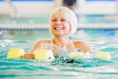Frau trainiert mit Geräten im Wasser, damit das Schwimmen noch effektiver wird.