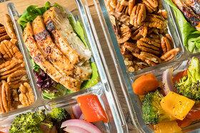 Meal Prep-Dosen gefüllt mit Gemüse, Fleisch und Nüssen.