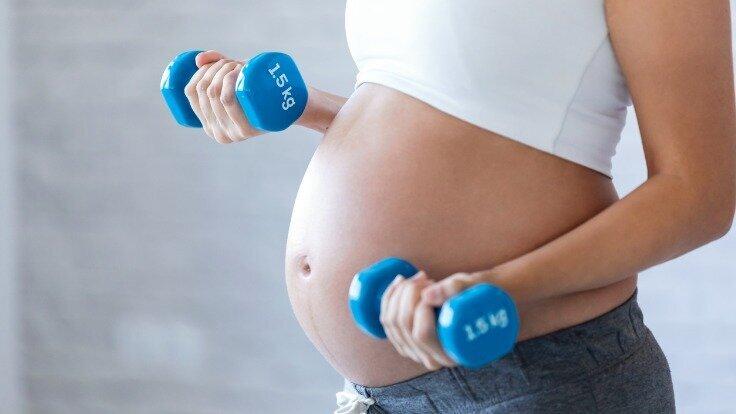 Eine schwangere Frau trainiert mit kleinen Hanteln
