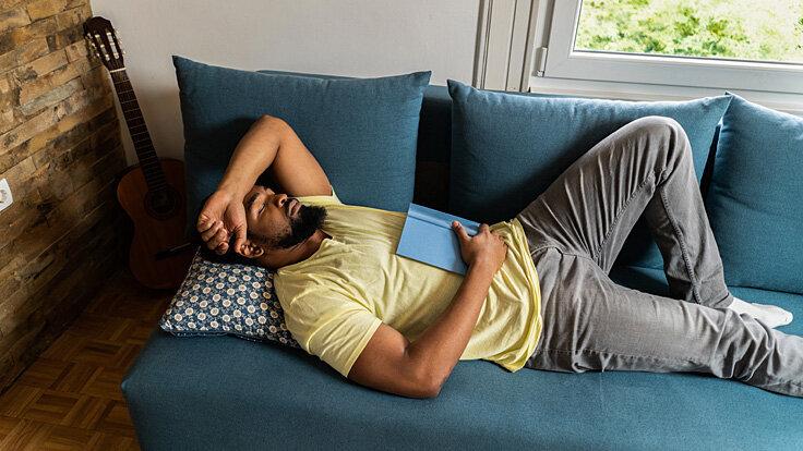 Ein Mann liegt auf dem Sofa und macht einen Powernap.