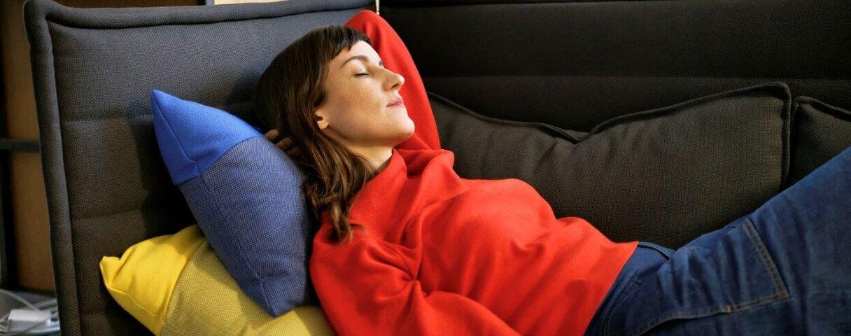 Junge Frau liegt auf einem Sofa und entspannt.