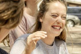Teenagerin lacht beherzt mit ihren Freunden, weil sie weiß, Lachen ist gesund.