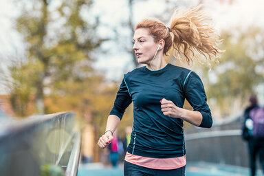 Eine junge Frau joggt über eine Brücke und hört dabei Musik.