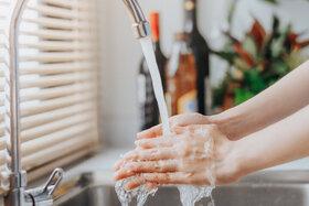 Frau spart kein Wasser und wäscht sich die Hände unter fließendem Wasser.
