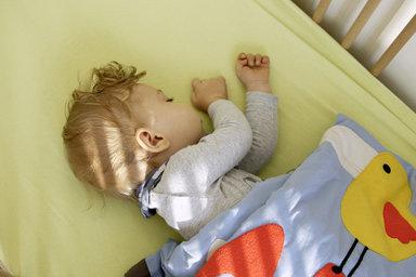 Ein Baby schläft im Babybett.