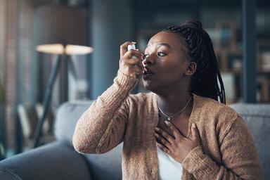 Eine Frau hat einen Asthmaanfall und Atemnot, darum benutzt sie ihr Asthmaspray.