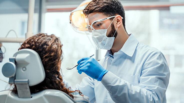 Ein Zahnarzt untersucht die möglichen Ursachen für den Mundgeruch einer Patientin.