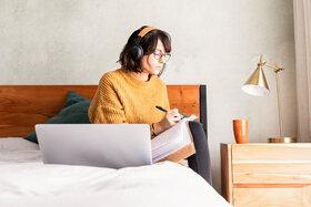Frau sitzt allein auf ihrem Bett, ist sie deshalb von Einsamkeit betroffen?