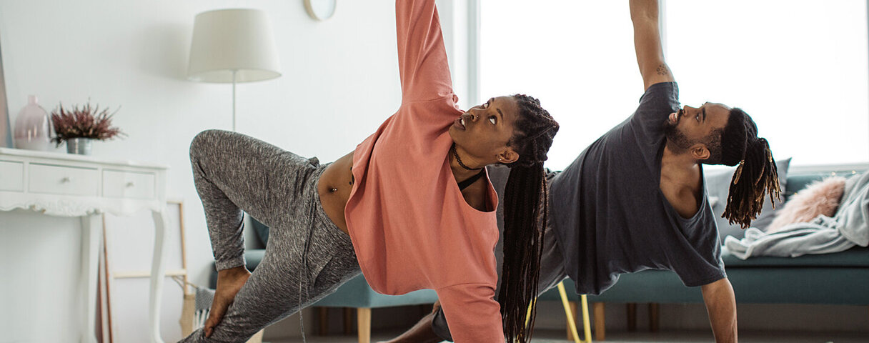 Ein junges Paar bleibt bei Rückenschmerzen in Bewegung und macht Übungen im Wohnzimmer.