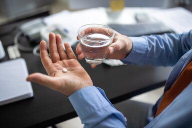 Ein Mann hält eine Schmerztablette und ein Glas Wasser in der Hand.