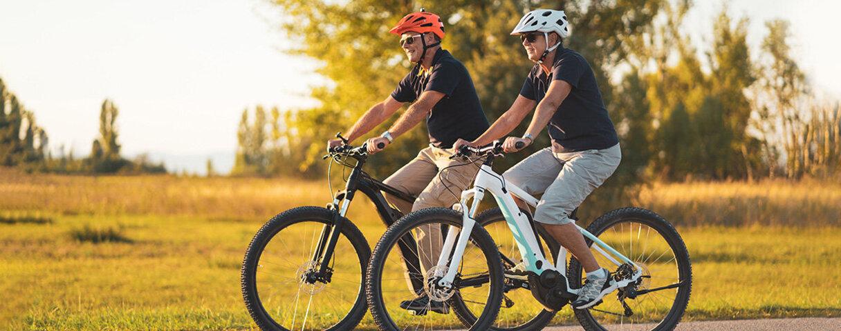 Senioren fahren mit dem E-Bike durch die Natur