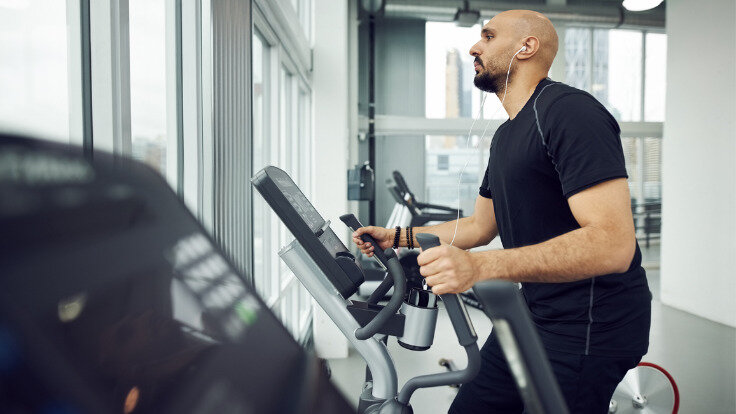 Mann treibt Sport im Fitnessstudio und geht seinem guten Vorsatz nach.