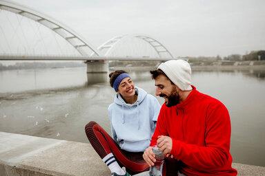 Zwei junge Menschen legen eine Joggingpause ein.