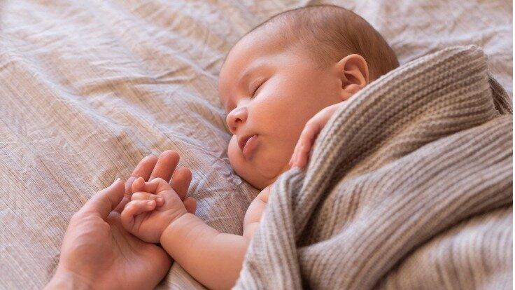 Baby liegt im Bett.