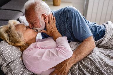 Ein älteres Paar liegt im Bett und schaut sich in die Augen.
