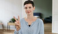 Junge Frau nimmt regelmäßig an Vorsorgeuntersuchen teil und zeigt mit Mittel- und Zeigefinger ein V, das für Vorsorge stehen soll.