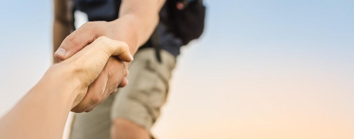 Ein Wanderer reicht einem anderen die Hand, um ihm beim Aufstieg zu helfen