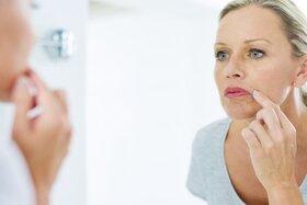 Eine Frau betrachtet ihren Lippenherpes im Spiegel