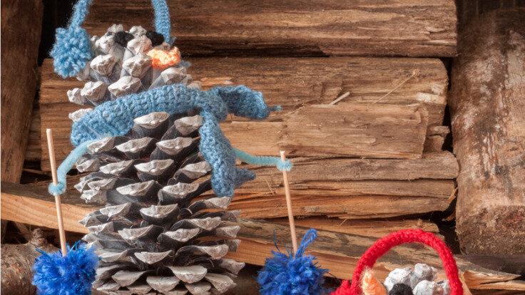 Zwei kleine Skifahrer aus Tannenzapfen gebastelt und mit Ohrenwärmer und Schal dekoriert.