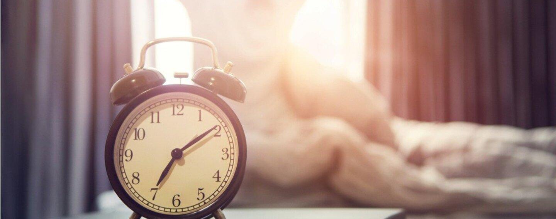 Eine Frau streckt sich am frühen Morgen gut gelaunt und dem Fenster zugewandt auf Ihrem Bett