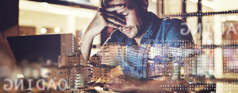 Ein Mann sitzt im Büro mit gesenktem Kopf vor seinem Laptop.