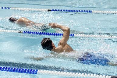 Zwei Männer ziehen im Schwimmbad Bahnen