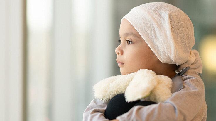 Ein Kind steht am Fenster und hält einen Teddybär fest. Es trägt ein Kopftuch und ist an Leukämie erkrankt.