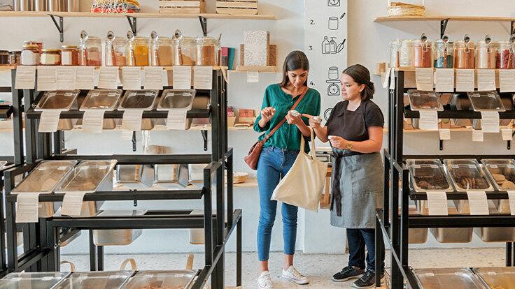 Frau lässt sich im Unverpackt-Laden von einer Mitarbeiterin beraten.