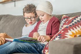 Ein gesundes Kind sitzt mit seinem erkrankten Geschwisterkind auf der Couch und liest ein Buch.