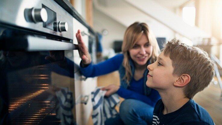 Mutter erklärt ihrem Sohn, dass der Backofen heiß ist und zeigt so feste Grenzen im Haushalt auf.