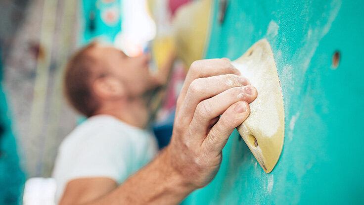 Mann beim Bouldern in einer Boulderhalle hält sich an Griff fest.