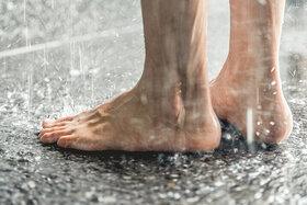Jemand steht in einer Dusche, wo Fußpilz leicht übertragen werden kann.