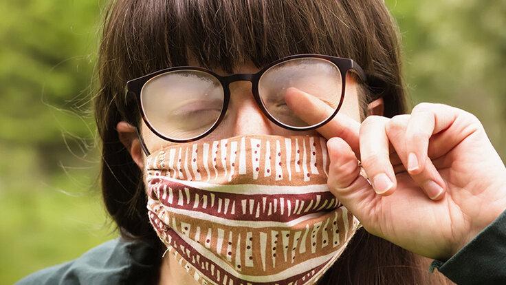 Eine Frau trägt Maske und Brille, doch diese ist beschlagen.