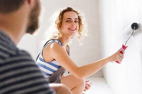 Ein Paar streicht eine Wand weiß.