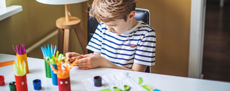 Ein Kind bastelt aus Müll Stifthalter.