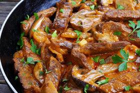 Pilzgericht mit Fleisch und Soße in einer schwarzen Bratpfanne angerichtet