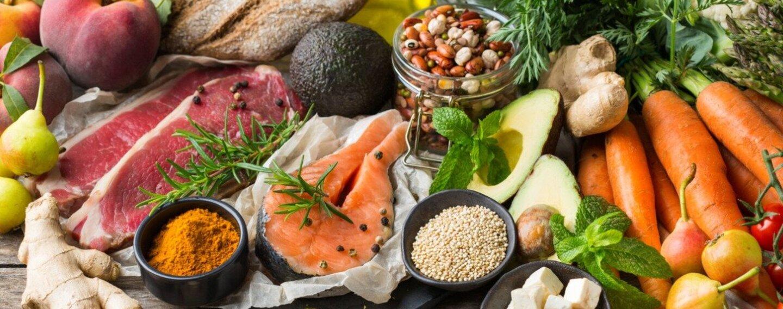 Auswahl an Lebensmitteln für eine ausgewogene Ernährung auf einem hölzernen Küchentisch.