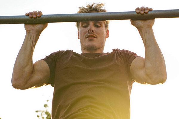 Ein junger Mann trainiert mit Klimmzügen seine Muskeln und stärkt damit seine Gesundheit
