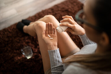 Frau nimmt Vitamin-B12-Tablette ein.