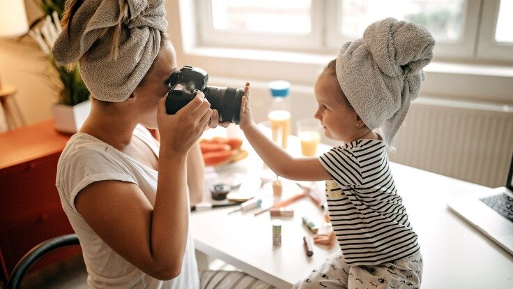 Eine Mutter macht ein Foto von ihrem Kind.