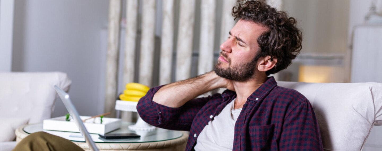 Mann sitzt auf dem Sofa und hat Nackenschmerzen nach einem langen Arbeitstag am Laptop.