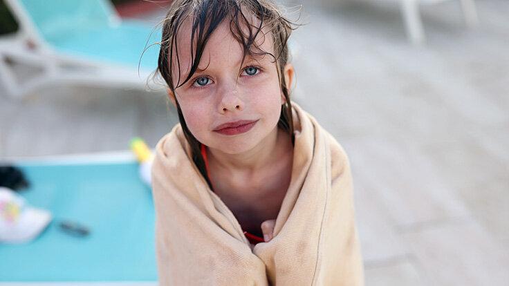 Ein junges Mädchen friert nach dem Baden.