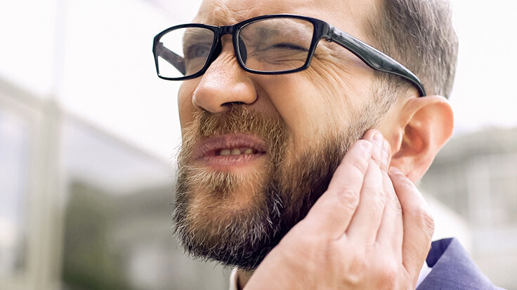Mann hält sich das Ohr, weil er an einem Tinnitus leidet.