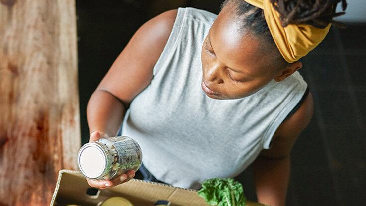 Frau schaut sich die Nährwerte auf ihrem Produkt an, bevor sie es zubereitet.