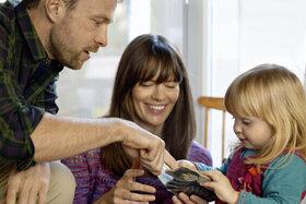 Vater, Mutter und Kind verbringen eine entspannte Zeit miteinander.