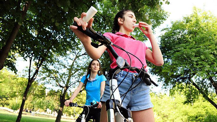Eine Frau benutzt beim Joggen mit Asthma ihr Asthmaspray.