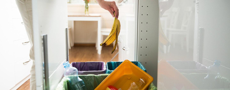 Eine Person überlegt, in welchen Müll die Bananenschale gehört.